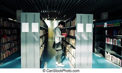 Young male student walking in a library. - Young handsome...