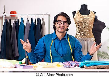 Young male tailor working at workshop