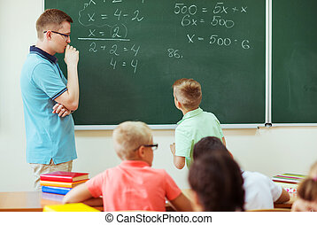 Young male teacher explaining math at the blackboard during a lesson at school