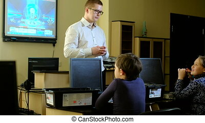 Young, male teacher helping his students build a robot 4k -...