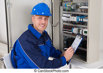Young Male Technician Examining Fusebox