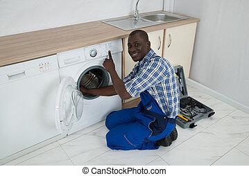 Young Male Technician Fixing Washing Machine