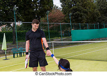 Young male tennis player helps his female partner to stand up