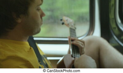Young male tourist playing ukulele in car