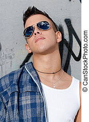 young male urban fashion sky on sunglasses over wall