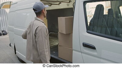 Young male van driver with a warehouse delivery
