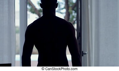 Young male with a beautiful body in swimming trunks coming out of the dark room to the street to the pool, slow motion