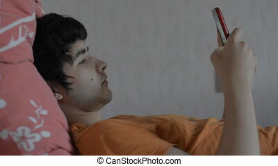 Young male with a smartphone lying on the bed
