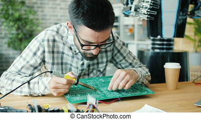 Young male worker fixing robot motherboard with soldering ...