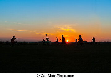 Young males practicing and training at soccer at twilight
