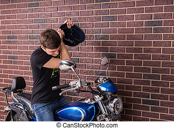 Young Man About to Beat his Motorbike with Helmet