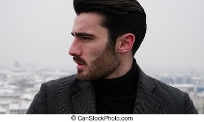 Young man above snowy cityscape in Italy - Handsome young...