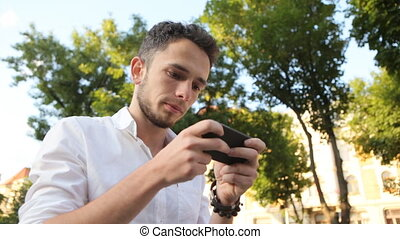Young man actively typing a message on his smartphone.