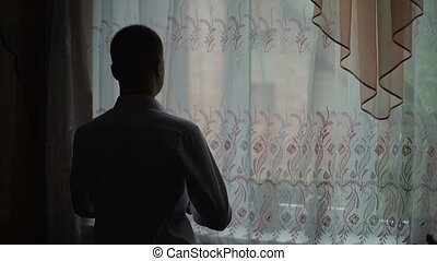 Young man admire view from window at home and put on a...