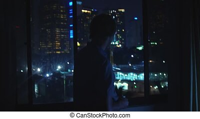 Young man admires view from window at home at night and...