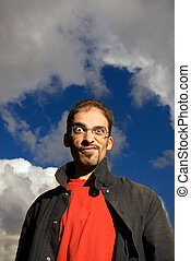 Young man against blue cloudy sky
