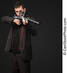 Young Man Aiming With Rifle against a black background
