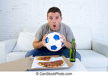 young man alone holding ball and beer bottle watching football game on television at home sofa couch