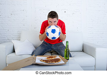 young man alone holding ball and kissing it in stress wearing team jersey watching football tv