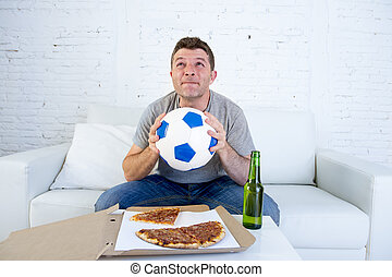young man alone in stress watching football game on television praying nervous and excited