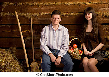 young man and beautiful woman near basket of fruit sitting on bench in wooden log hut