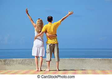 young man and beautiful woman on quay lifted hands upwards