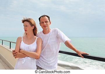 young man and beautiful woman on veranda near seacoast