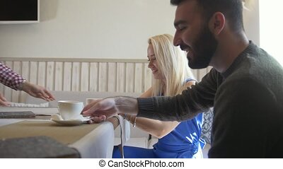 Young man and blonde woman takes the cups of coffee at the cafe