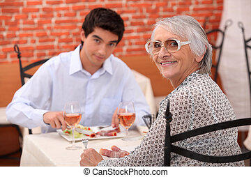 Young man and elderly woman in a restaurant