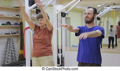 Young man and elderly woman stretching out, doing exercises in fitness room. Healthy gymnastics. Active people.