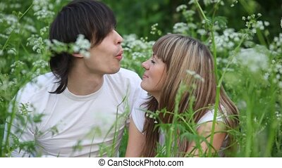 young man and girl blowing dandelions on each other and laughing