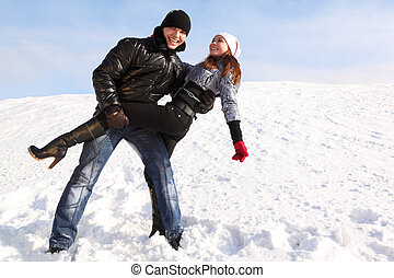 young man and girl dance on snowy area and smiling, man looking at camera