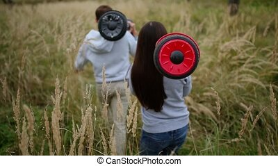Young man and girl go into the field with hoverboards look...