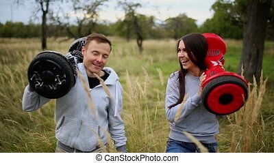 Young man and girl go into the field with hoverboards look at one another in urban clothing. Steadicam