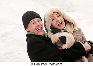 young man and girl in warm dress laughing, embracing and looking at camera, half body, winter day
