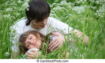 young man and girl laying on grass and playing with each other