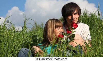 young man and girl smelling flowers and kissing each other