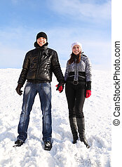 young man and girl standing on snowy area, holding for hands and smiling, looking at camera