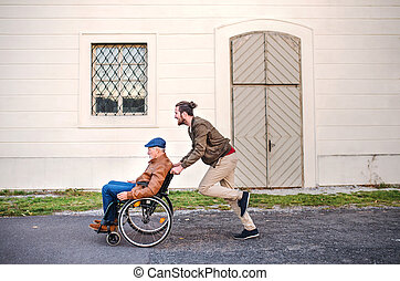 Young man and his senior father in wheelchair on a walk in town, having fun.