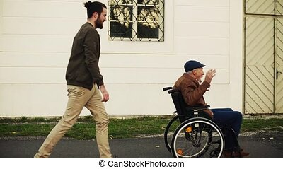 Young man and his senior father in wheelchair on a walk in...