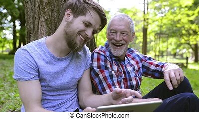 Young man and his senior father with tablet outdoors. -...