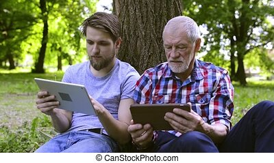 Young man and his senior father with tablets outdoors.