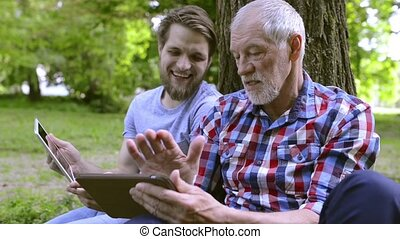Young man and his senior father with tablets outdoors. -...