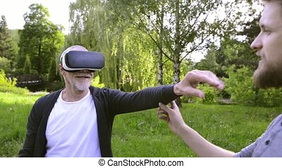 Young man and his senior father with VR glasses outdoors. -...