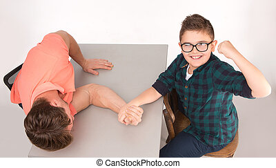 Young man and his son arm wrestling - Boy in glasses looking...