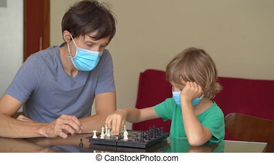 Young man and his son play chess at home during the quarantine. Self-isolation with kids