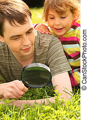 young man and little girl look through magnifier