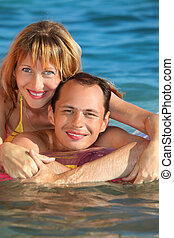 young man and nice women lying on an inflatable mattress in pool, woman lying astride man