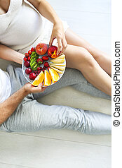 Young man and pregnant woman sitting with fruit plate