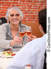 Young man and senior woman having lunch in a restaurant